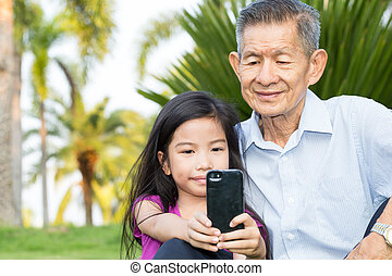 Grandfather and grandchild making selfie with smart phone in the park