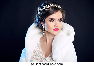 Hairstyle. Winter Girl in Luxury fashion Fur Coat. Hair styling. Makeup. Beautiful model woman in White Fur isolated on black background. diamond jewelry.