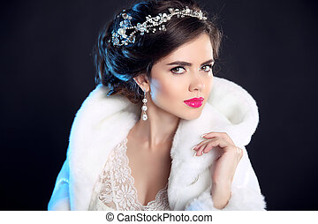 Makeup. Beauty Winter portrait of fashion girl  in white Fur Coat. Hairstyle. Elegant woman isolated on black background. Luxury Jewelry.
