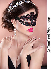 Beauty fashion girl model with mask. Makeup. Hairstyle. Jewelry. Sensual woman wearing venetian masquerade carnival mask