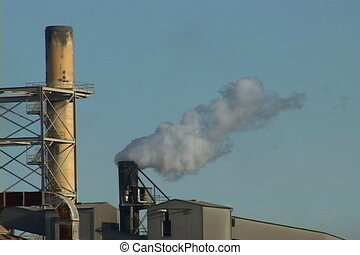 Factory Emissions - Smoke and steam billow from a factory...