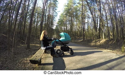 mom sit bench child buggy - young blonde mother sit on park...