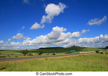 cloudy day - clouds casting a shadow on a field on a cloudy...