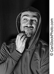 Man In Doubt - Man wearing, hood scratching his beard,...