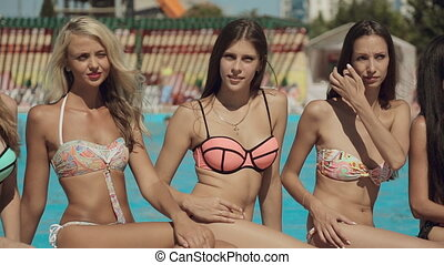 Sexy models wearing bikini sitting by the pool in the summer