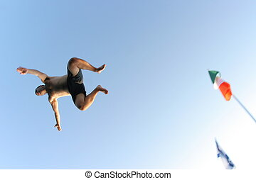 Flying - Man jumps off a dock, soaring over camera