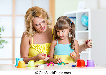 kid girl and mother playing colorful clay toy