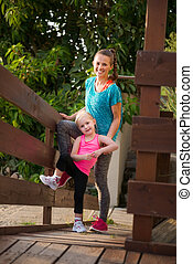 Happy young mother and daughter standing on wood bridge at...