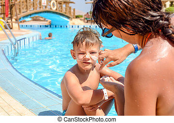 Mother putting sunscreen on her sons face