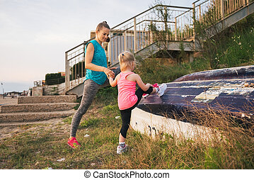 Mother showing daughter how to stretch using a boat on the beach