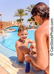 Woman applying sunscreen to the face of her son