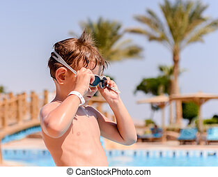 Young boy putting on his swimming goggles