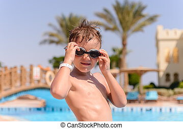 Young boy putting on goggles to go swimming