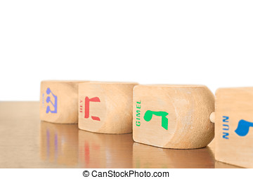 4 Chanukah wooden dreidels in a row laying on a wood surface...