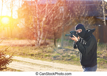 Gunman in black mask holding gun with silencer