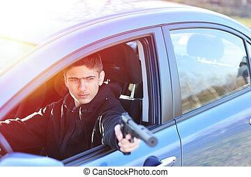Gunman in car holding gun with silencer