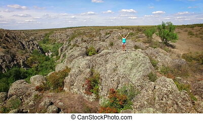Aerial: Woman on the rock