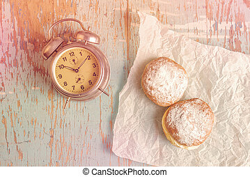 Sweet sugary donuts and vintage clock on rustic table -...