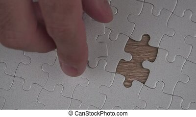 Solving jigsaw puzzle - Male hand putting a missing piece...
