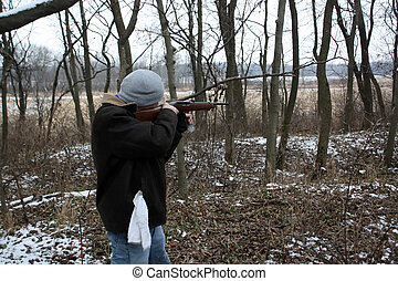 man with rifle - a man shooting a rifle in the woods