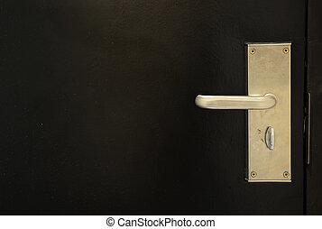 Metal door handle on black door background