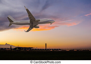 Commercial airplane flying over the airport at sunset