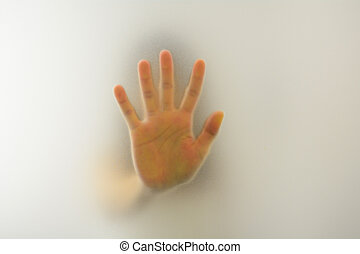 Woman's hand behind blurry glass