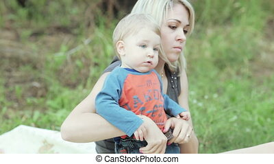 Mother and son on nature - Nature baby boy eating biscuits...