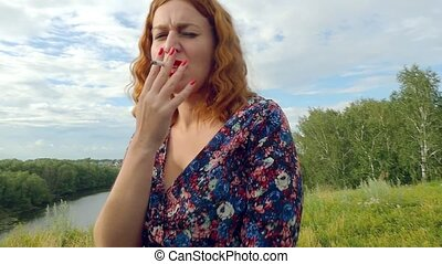 young curly red-haired woman smokes cigarette on the nature...
