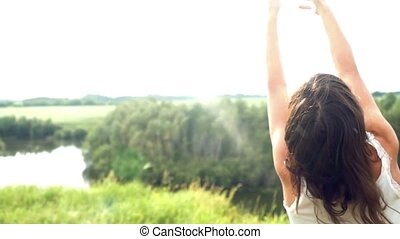 Happiness young beautiful brunette woman raises her arms outdoor under sunlight of sunset spinning around and dancing in the rain