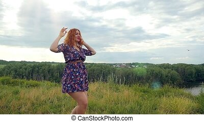 Young curly red-haired woman dancing happy in summer meadow. dragonfly flying on background