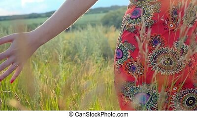 red-haired woman in long dress walking in a field touching...