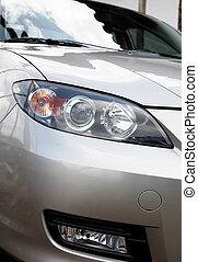 Car lights - Headlights of a gray car, over green background