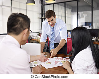 multinational businesspeople discussing sales performance in...