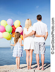 happy family at the seaside with bunch of balloons