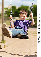 happy little boy swinging on swing at playground - summer,...