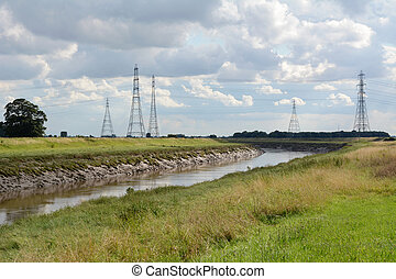 Overhead power lines span the River Nene in Cambridgeshire -...