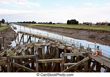 Approach on River Nene at low tide to Crosskeys Bridge at Sutton Bridge, Lincolnshire. Intricate wooden construction supports walkway with lifebelts at the ready.