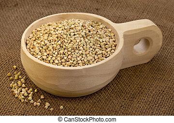 scoop of buckwheat groats - buckwheat groats on a rustic...