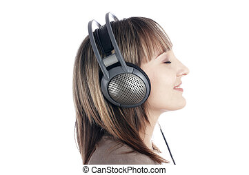 The young charming smiling girl listens to music in...
