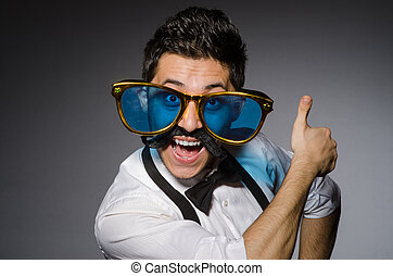 Young caucasian man wearing sunglasses against gray