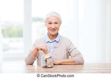 senior woman putting money into glass jar at home - savings,...