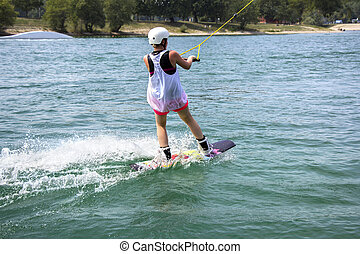 Young girl wakeboarder in action on the lake
