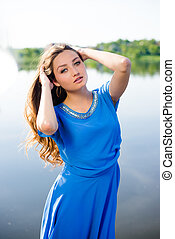 Young beautiful surprized girl standing by river touching...