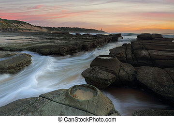 Ocean flowing in and out of the rock chasm Norah Head -...