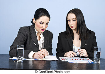 Businesswomen in office write at meeting