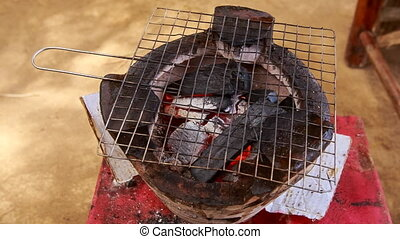 view of wooden coal flame in outdoor grill and food grating...