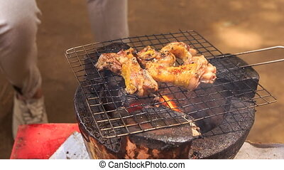 closeup view of fried chicken on grating of outdoor grill -...