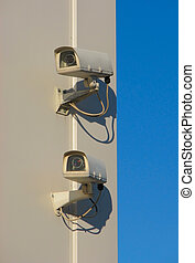 Two security cameras mounted on wall