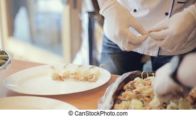 Waiter in gloves puts on a plate appetizing canapes of...